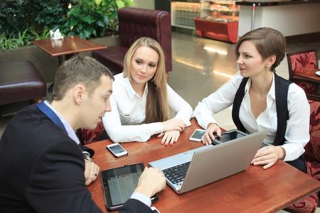 Waitress taking order from businessmen in cafe smiling laptop work