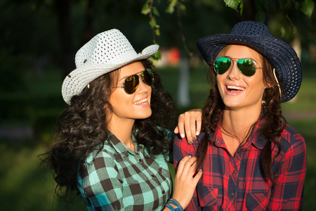 Two attractive girls in cowboy hats and sunglasses walking in the park. 免版税图像