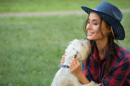 toyterrier: Smiling girl with her small dog. cowboy hat and plaid shirt. Outdoodrs.
