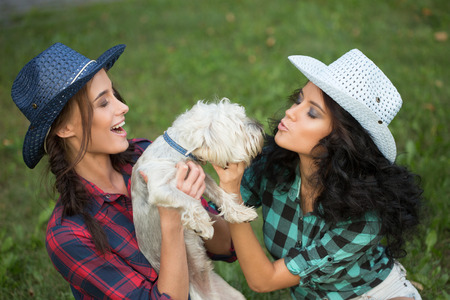 toyterrier: Two girls walking with his dog. cowboy hat and plaid shirt. Outdoodrs. Stock Photo