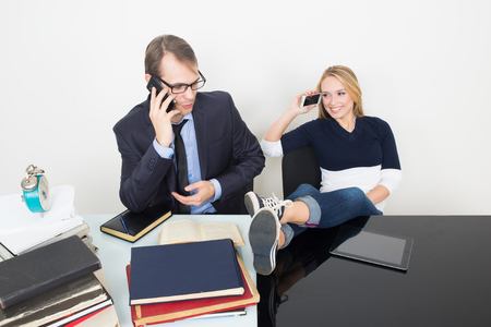 woman prevents a man to work. talking on the phone. It distracts from the business.