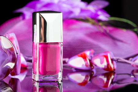 manicure and pedicure: magenta nail polish on the background of womens accessories