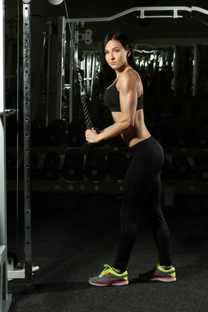 bra: fitness woman doing triceps exercises in the gym. Brunette fitness girl in black sport wear with perfect body in gym exercising