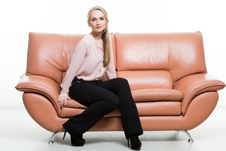 nonverbal communication: Elegant beautiful woman sitting on a couch a leather. isolated on white. Training managers. sales agents. non-verbal communication. Stock Photo