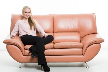 comunicacion no verbal: Hermosa mujer elegante que se sienta en un sofá de cuero. aislado en blanco. Los administradores de formación. agentes de ventas. comunicación no verbal.