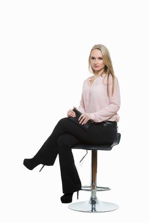 comunicacion no verbal: Mujer hermosa elegante sentado en una barra de metal contemporáneo heces. aislado en blanco. Los administradores de formación. agentes de ventas. comunicación no verbal. Foto de archivo