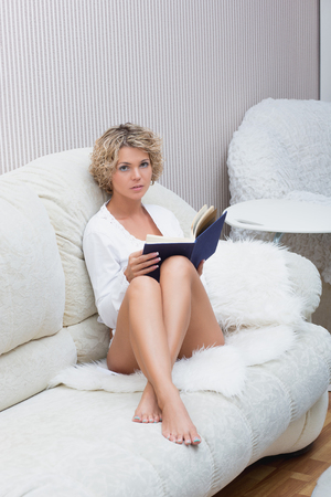poem: sexy blonde girl reading a book lying on a sofa Stock Photo