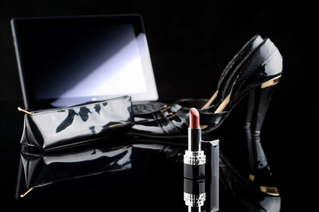 comprando zapatos: laptop, lipstick and shoes. on a black background. female set. Online buying cosmetics