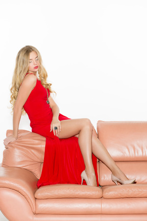 red sofa: full-length portrait of beautiful young blond woman on couch