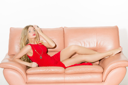 full-length portrait of beautiful young blond woman on couch