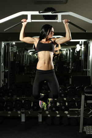pull up: Sexy hot Brunette fitness bikini girl with perfect shape body making elevations pull up in gym Stock Photo