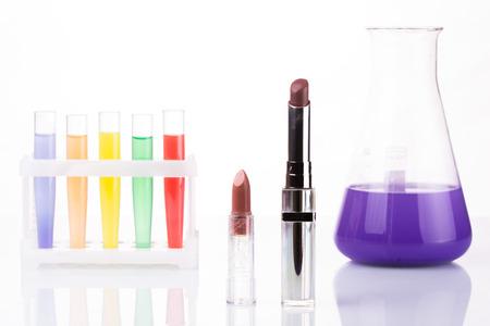 harmful: chemical test tubes and lipstick. White background. harmful cosmetics. Stock Photo