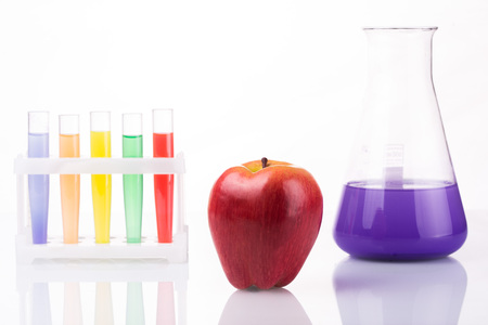 pesticides: Fruit close chemical test tubes. Genetic Engineering. pesticides in foods. White background.