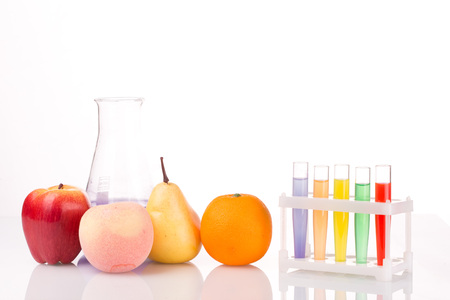genetic engineering: Fruit close chemical test tubes. Genetic Engineering. pesticides in foods. White background.