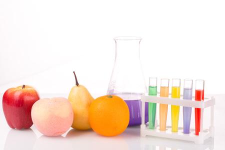 Estrechos tubos de ensayo químico de frutas. Ingeniería genética. plaguicidas en los alimentos. Fondo blanco.