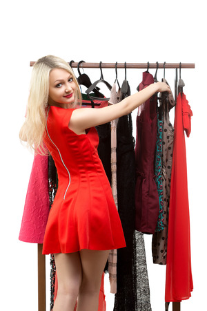 sexual selection: beautiful girl in a red dress in front of a clothes hanger. isolated on white background