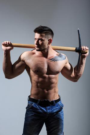 mattock: sexy Muscular man holding pickaxe. working stone mines.