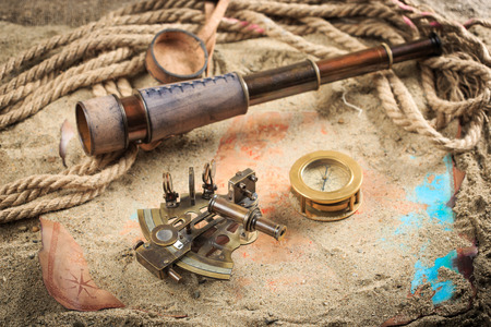 cordage: a set of nautical instruments, lying on the sand and old map.