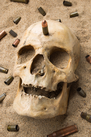 cadaver: skull lying in the sand, scattered rifle and pistol cartridges