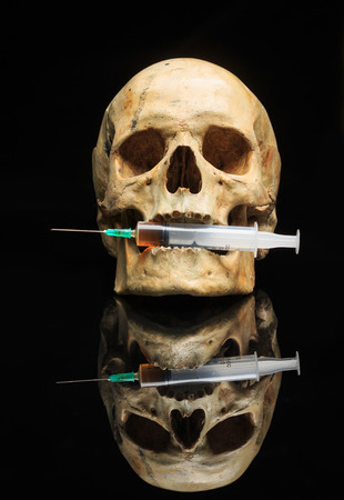 Skull and syringe of yellowish liquid . The syringe is filled with medicine , poison or drugs. Isolated on black Stock Photo