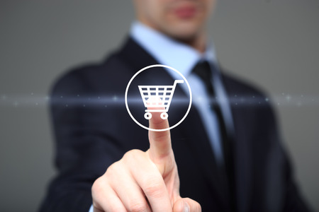 Online shopping  concept with businessman touching virtual shopping cart.  business, technology, internet and networking concept
