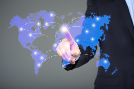 business globe: Portrait of pensive handsome businessman touching a world map on the screen showing global connection between different continents.