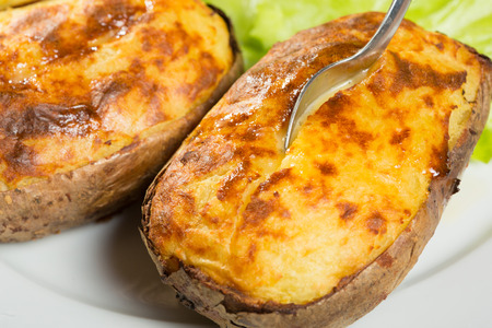 baked potatoes whole in their skins with butter and garlic