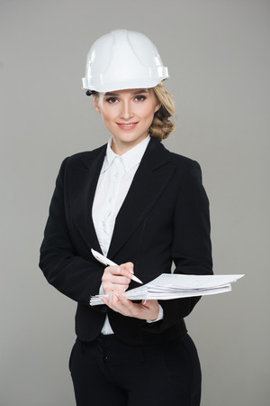 construction project: Woman architect with drawings. girl in a building helmet Stock Photo
