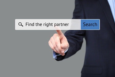 businessman presses a button in the browser - to find a partner. internet concept