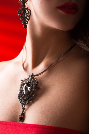 fake diamond: necklace on female neck. girl holding hands. sexy red lips. close-up