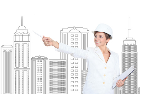 female child: Smiling businesswoman in helmet studying the sketch of future business centre. Attractive lady in business suit is satisfied by the plan made by architect. Stock Photo