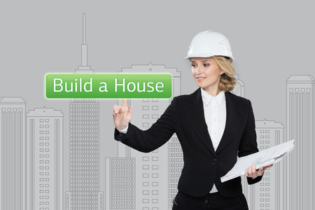 press agent: Business woman pressing build a hause button on virtual screens. Residential Blocks. Business, technology and networking concept