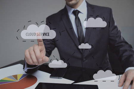 pressing: Businessman pressing high tech glowing modern cloud service interface touch screen button