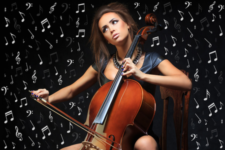 recital: Pretty young female musician playing the cello at a classical recital concentrating on her notes in the darkness, close up view Stock Photo