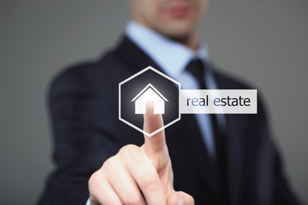 Geschäfts-, Technologie-, Internet- und Vernetzungskonzept - Geschäftsmann, der Immobilientaste auf virtuellen Schirmen bedrängt