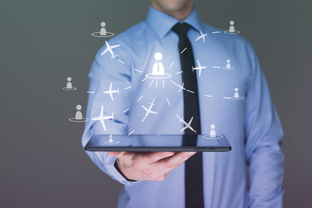 flightpath: businessman holding a tablet pc. It shows planes. travel and travel