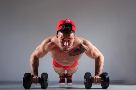 pushed: Muscular bodybuilder guy doing exercises with dumbbells. pushed Stock Photo