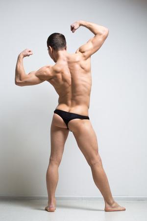 sixpack: Shirtless athletic man turned back on white background.