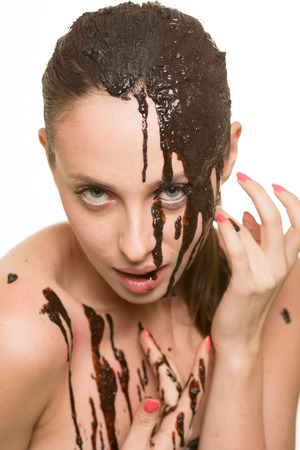 beautiful girl bathed in chocolate. on a white background