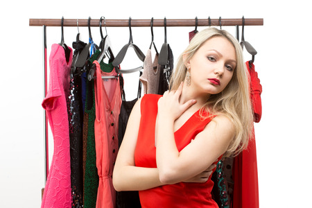 beautiful girl in a red dress in front of a clothes hanger. isolated on white background