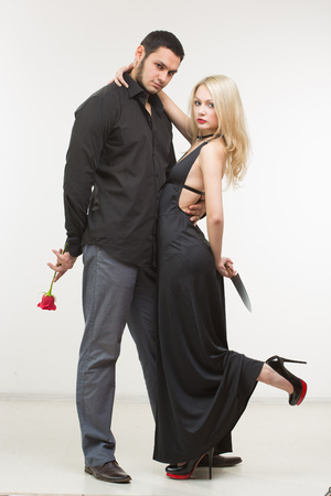 meanness: girl holding knife traitor. man with rose in his hand. white background Stock Photo