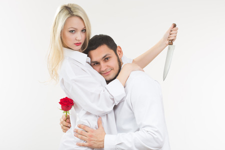traitor: girl holding knife traitor. man with rose in his hand. white background Stock Photo