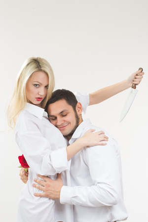girl holding knife traitor. man with rose in his hand. white background Stock Photo