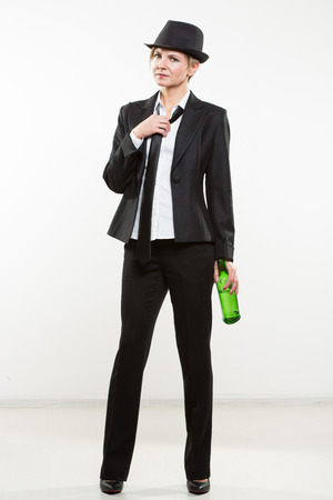Happy elegant woman in a business suit, holding bottle of alcohol. Stock Photo