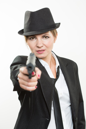 venganza: beautiful girl gangster holding a gun. Classic suit and hat. isolated on white background. red nail polish