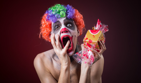 scary clown with spooky makeup and more candy in the hands