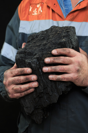 extracted: Coal miner showing lump of coal with thumbs up against a dark background Stock Photo