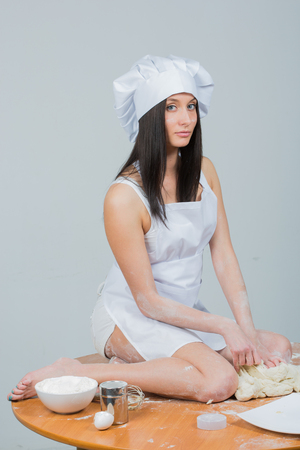 sexy woman in chef uniform knead the dough on white background