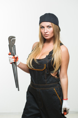 Nice sexy woman mechanic holding wrench. isolated on white background Stock Photo