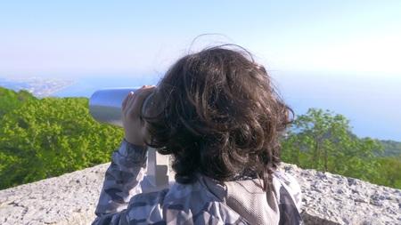 boy teenager, traveler, looking through a telescope on top of a mountain Stock Photo